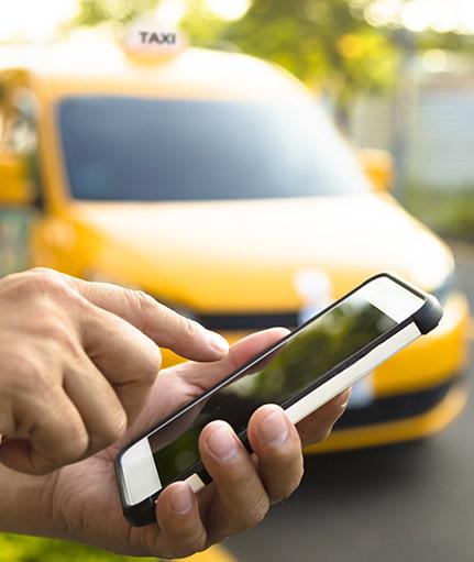 Finger tippt auf Smartphone im Hintergrund Taxi