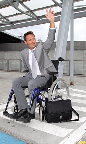 Mann im Anzug sitz in Rollstuhl und ruft Taxi