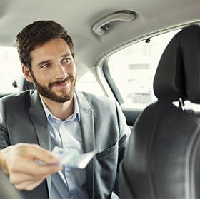 Mann in Anzug bezahlt in bar im Taxi