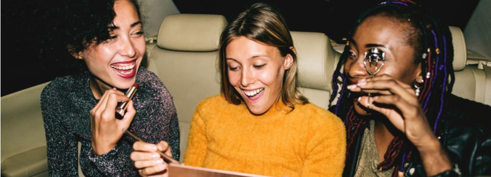 3 Frauen auf Rückbank in Taxi schminken sich